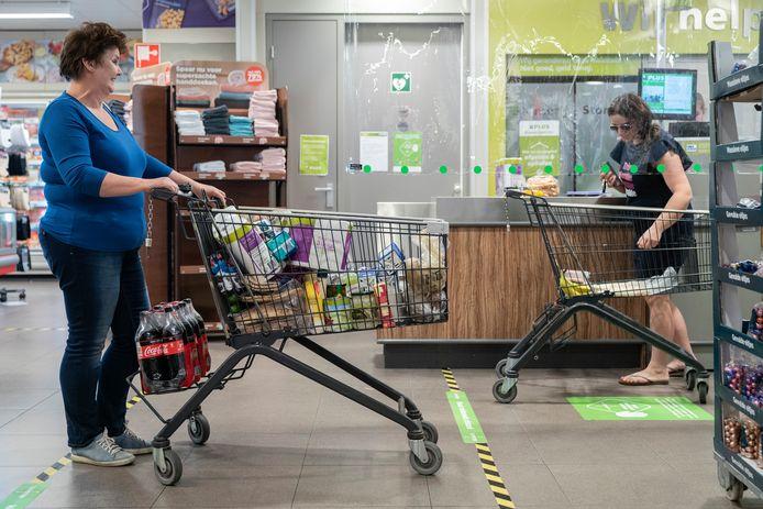 Strepen op de vloer bij de Plus Supermarkt geven de anderhalve meter afstand aan.