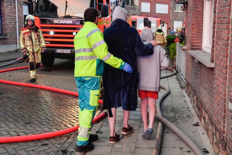 De broers worden weggeleid door een brandweerman.