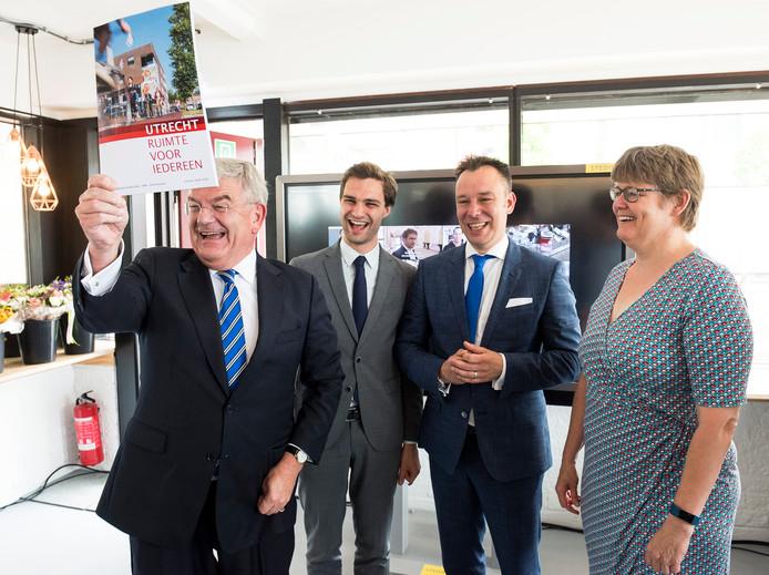 Burgemeester Jan van Zanen houdt het nog verse coalitieakkoord omhoog, gemaakt door de onderhandelaars Maarten van Ooijen (ChristenUnie), Klaas Verschuure (D66) en Heleen de Boer (GroenLinks).