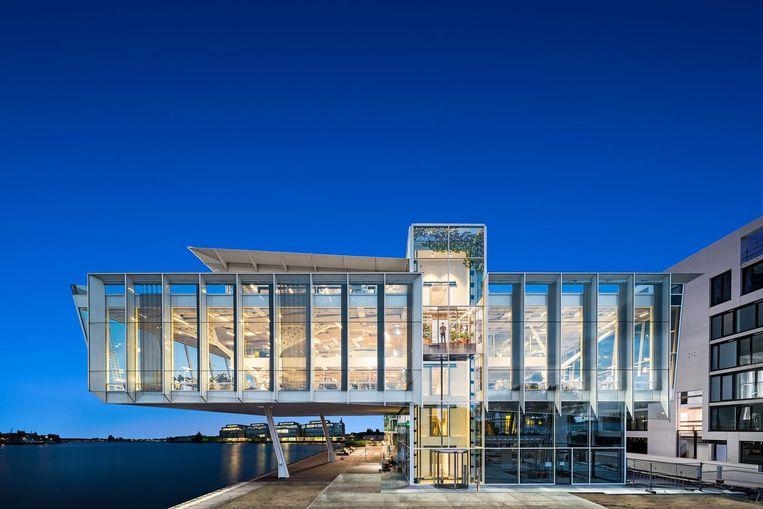 Het nieuwe hoofdkantoor van ontwikkelaar Amvest leunt op twee schuine kolommen en steekt zo de Entrepothaven in Beeld Studio de Nooyer