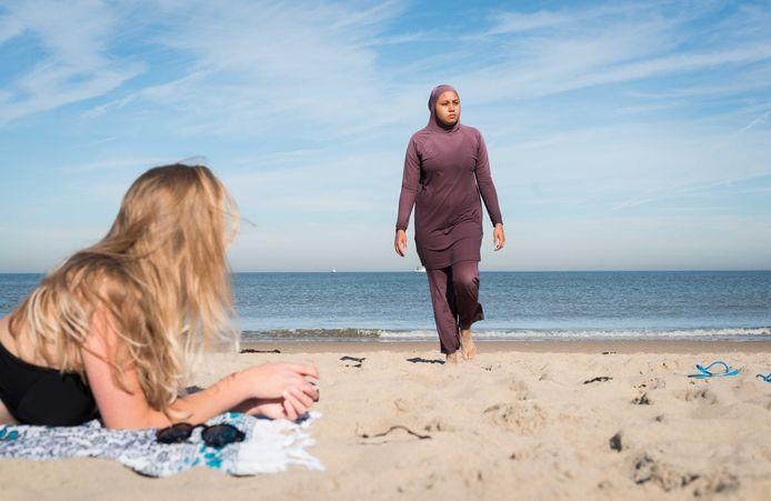 Een meisje in bikini kijkt toe terwijl een vrouw in boerkini de zee verlaat. Foto ter illustratie.