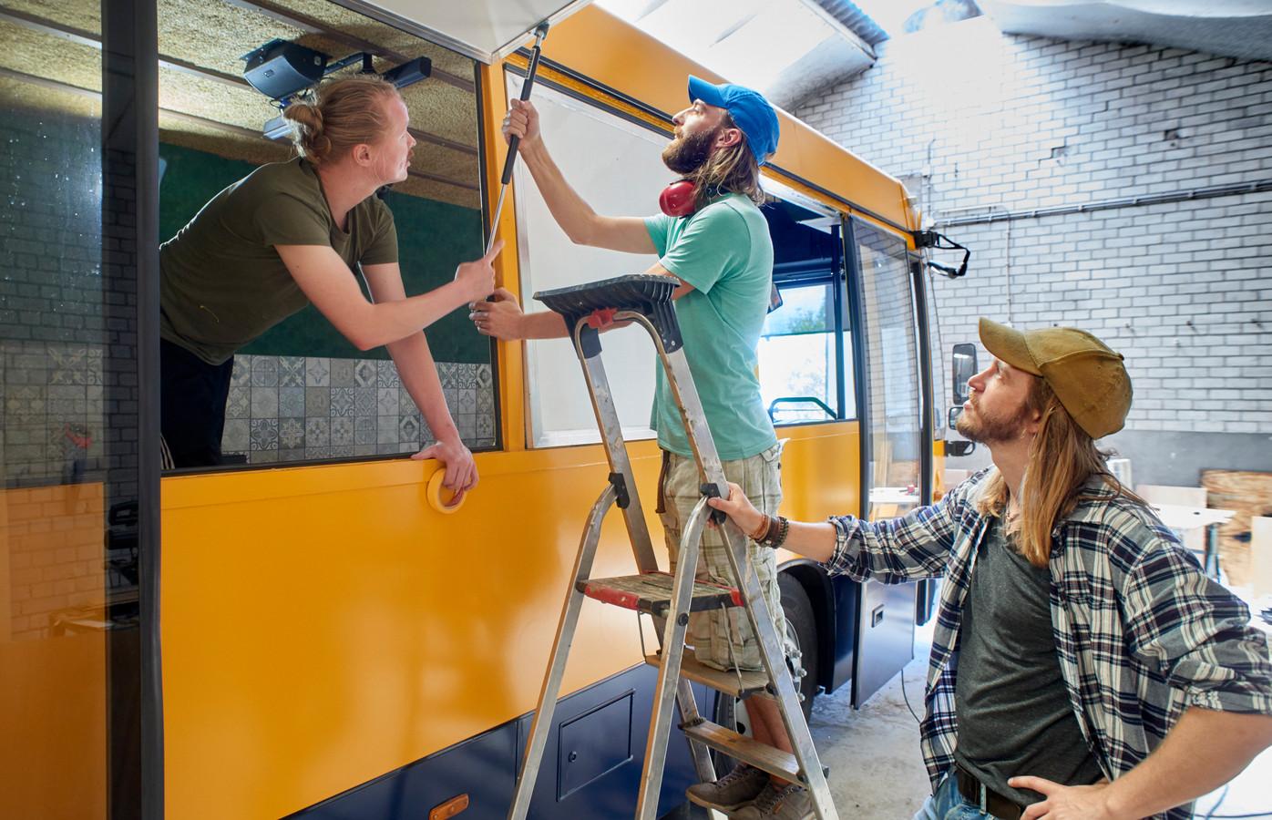 Sander Ottens, Frank en Niels van den Bogaert bezig met een van de luiken van hun bus.