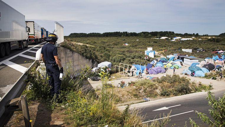 Vrachtwagens rijden voorbij het 'Jungle' migrantenkamp in Calais. De politie probeert vluchtelingen die op de trucks willen klimmen tegen te houden.