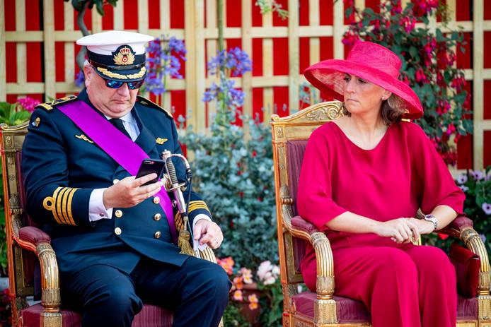 Prins Laurent is druk met zijn telefoon