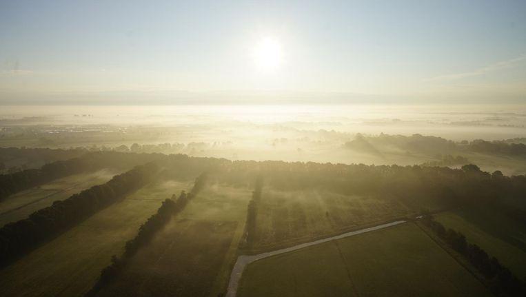 De zon komt op in de mist boven het Friese platteland. Beeld anp