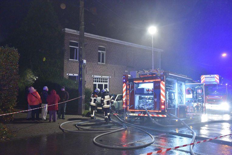 Buren kijken toe hoe de brandweer de brand bestrijdt.