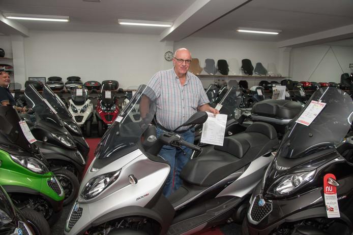 Arjan Brouwer bij de bestelde scooter waarop hij allerlei extra accessoires zette voor de klant.