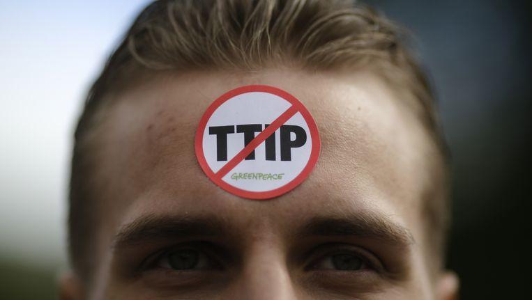 Demonstrant tegen TTIP met een sticker van Greenpeace. Beeld ap