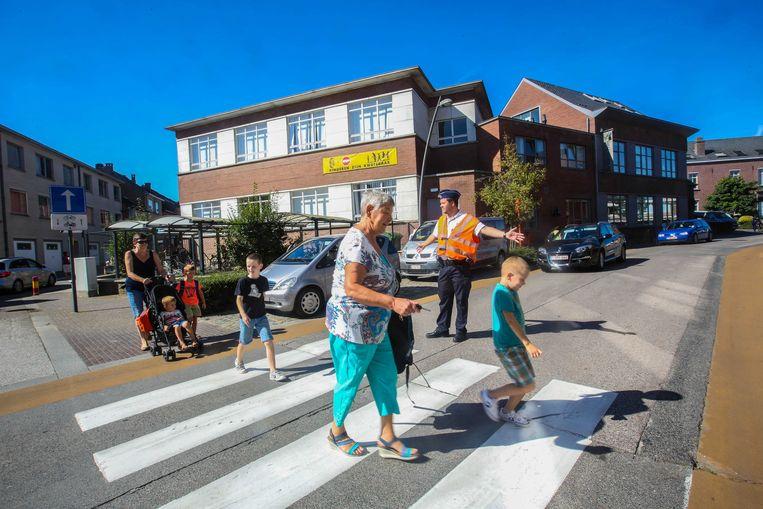 Een agent helpt bij het oversteken ter hoogte van De Kleine Prins. Hoewel het een zone 30 is, waar voetgangers altijd voorrang hebben, werden er toch zebrapaden geschilderd.