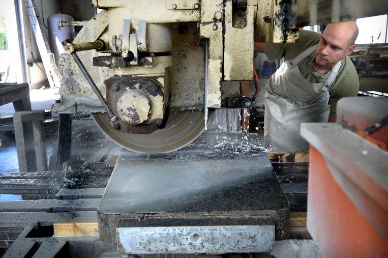 Henk Lavrijsen verwijdert in zijn Atelier Lamier de naam van een oude grafsteen. Beeld Marcel van den Bergh