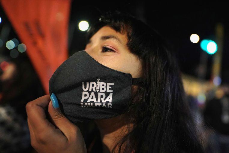 Een tegenstander van Uribe met een mondmaskertje met de tekst 'paramilitaire Uribe'.