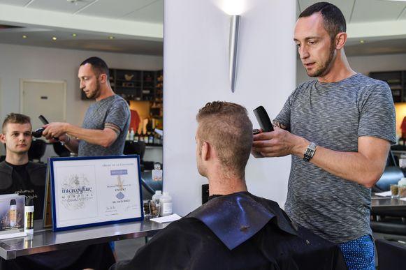 Tom in zijn salon met de oorkonde voor de spiegel.