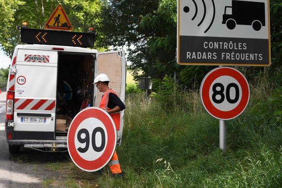 28 juni 2018: een wegenwerker vervangt aan een Franse departementale weg  het 90 km/h-bord door een 80 km/h-bord.