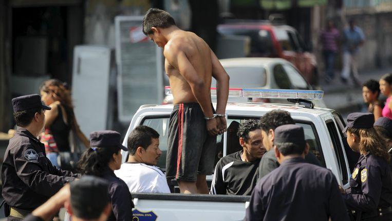 Politie-agenten transporteren vermoedelijke leden van de de 'Barrio 18 gang' naar de gevangenis van San Salvador.