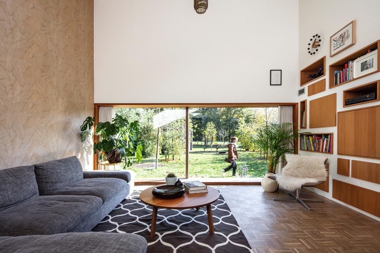 Hans tekende in het salon een laag raam, dat de hoge ruimte benadrukt en uitnodigt om te gaan zitten. Achter de deurtjes van de 'pêle mêle'-kastenwand zit onder meer een tv, een drankkast en een poezenhokje.