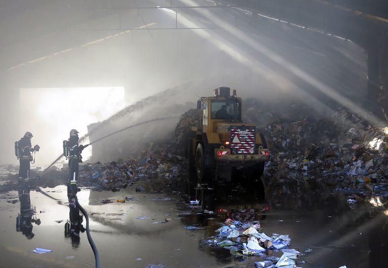 Brandweerlui blussen het papier in de loods, een bulldozer voert het naar buiten.