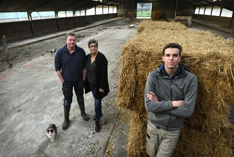 Bram van Beekveld en zijn ouders in de lege koeienstal.  Beeld Marcel van den Bergh