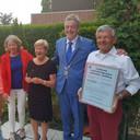 Oud-burgemeester Fons Naterop reikt in de gemeente Aalburg een oorkonde uit.