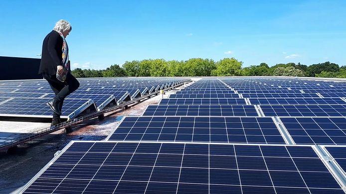 Wethouder Klaar Koenraad tussen de zonnepanelen op het dak van het JTC.