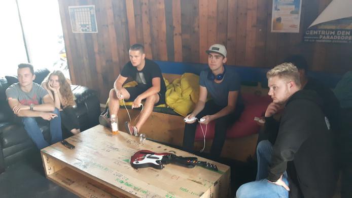 De jongeren spelen tijdens de inloopavond een videogame.