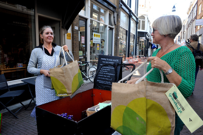 Annette de Vlieger (rechts) brengt wekelijks groentepakketten uit eigen regio rond per bakfiets. Lokaal De Klik in het centrum is één van de afhaalpunten.