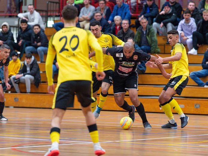 Reza Ngarigota van Futsal Apeldoorn neemt het op tegen drie opponenten van ASV Lebo.