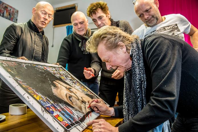Rocker Danny Lademacher signeert het schilderij dat Detmer Verburg (rechts) maakte van Herman Brood.