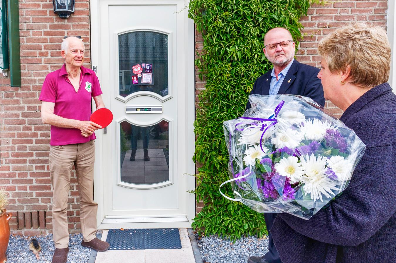 Harry Heuzen (76), links op de foto) is al 60 jaar lid. Hij draagt het shirt van de eerste competitiewedstrijd - hij past het nog. Voorzitter van de jubileumvereniging Piet van Egmond overhandigt een envelop, Laura van de Meer geeft een bos bloemen namens het bestuur.