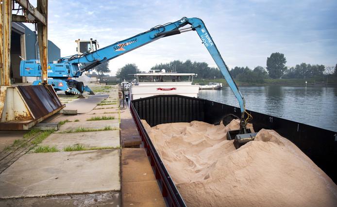 Een schip lost strooizout. Rijkswaterstaat is midden in de zomer al bezig met de bevoorrading van de zoutloodsen voor de komende winter.
