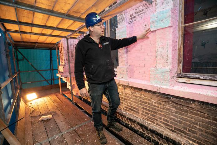 Uitvoerder Ben van der Loop van bouwbedrijf Dré van Dinther op de steigers bij het nu nog gedeeltelijk Roze Kasteel. De roze verf wordt met behulp van een pasta verwijderd.
