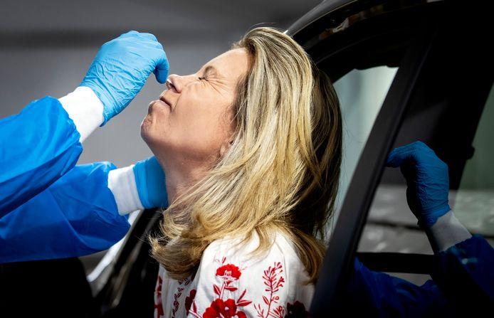 Een medewerker van de GGD Rotterdam-Rijnmond neemt een coronatest af in een teststraat. Het aantal besmettingen met het coronavirus blijft toenemen.