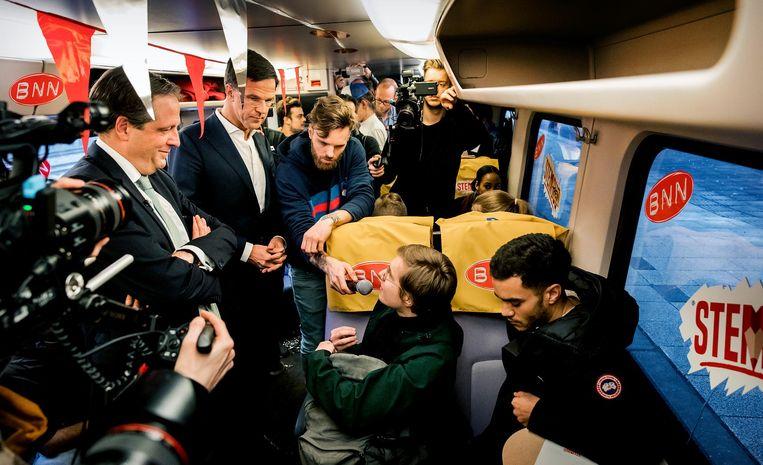 BNN-presentator Tim Hofman probeerde vorig jaar met Alexander Pechtold (D66) en Mark Rutte (VVD) jongeren in de trein over te halen te gaan stemmen. Beeld ANP