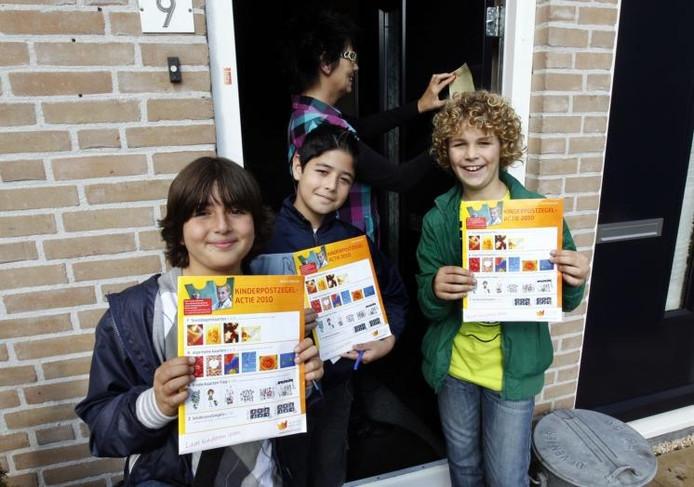 Archieffoto 2012: Kinderpostzegels verkopen geeft Ender Ascipinar, Danyal Sadeghpoor en Leon Kingma een goed gevoel. ,,Het is mooi om kinderen in arme landen te kunnen helpen.'' foto Ab Hakeboom