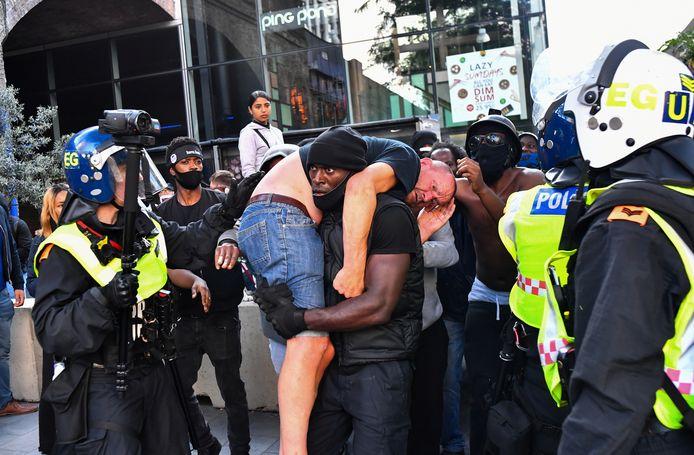 Een zwarte demonstrant draagt, geflankeerd door de politie, een gewonde tegen-demonstrant weg naar een veilige plek in de buurt van het Waterloo Station in Londen, tijdens een protest van Black Lives Matter.