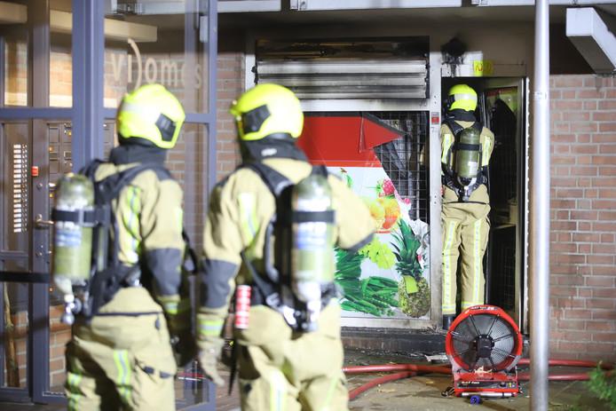 De brandweer ventileert de winkel waar de brand was.