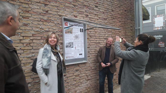 Het Joop Sarsplein is geopend. Sigrid Becker, de vrouw van Joop, maakt een foto van een speciale voor het plein gemaakte krantenpagina. Links wethouder Ingrid Lambregts, rechts provinciaal gedeputeerde Peter Kerris.