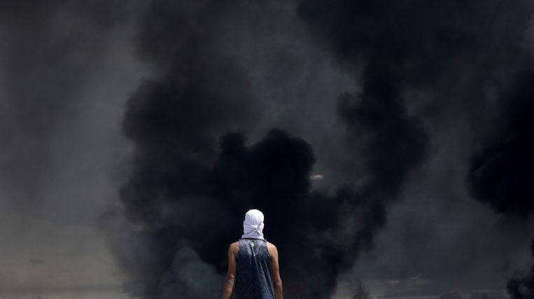 Een Palestijnse demonstrant staat voor een muur van rook tijdens een protest.