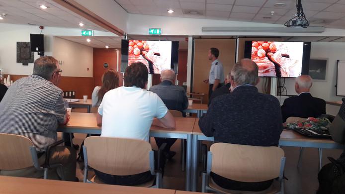 Hoofd verkeersleiding majoor Marcel de Pee presenteert de resultaten van de masterclass voor omwonenden van de vliegbasis.