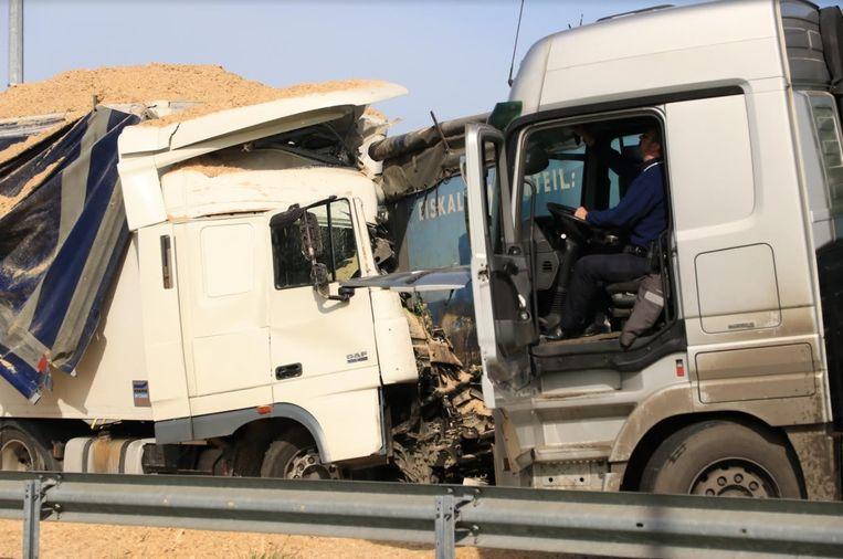 Een agent (rechts) doet vaststellingen in de aangereden Duitse vrachtwagen.  Door de klap draaide de truck en kwam zo tegenover de aanrijdende Nederlandse vrachtwagen te staan.