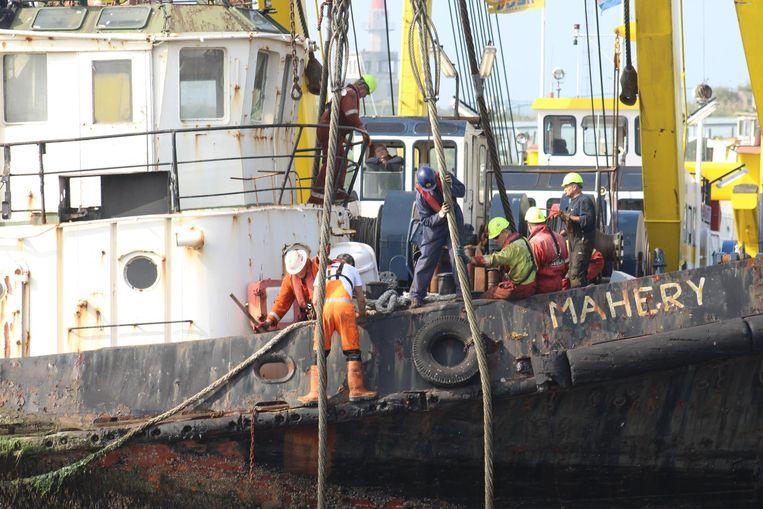 Werklui bevestigen kabels aan het schip.