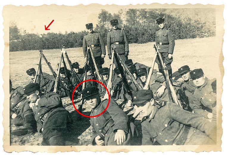 Op deze groepsfoto van zogeheten Trawniki, onder Sovjet-krijgsgevangenen geronselde helpers voor het vuile werk in de concentratiekampen, in Sobibor is de man die op de voorgrond in het midden ligt Iwan Demjanjuk. Links achter de bomen, precies boven de meest linkse driehoek van geweren, is volgens de Duitse organisatie Bildungswerk Stanislaw Hantz de schoorsteen van de gaskamers te zien met links daarnaast de gevel van de barak waar het haar van de vrouwen werd afgeknipt. Beeld United States Holocaust Museum