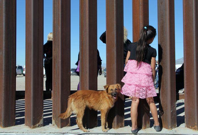 Een Mexicaans meisje bekijkt door de spijlen op de grens een demonstratie tegen deze muur in Sunland Park, in de VS Foto Herika Martinez