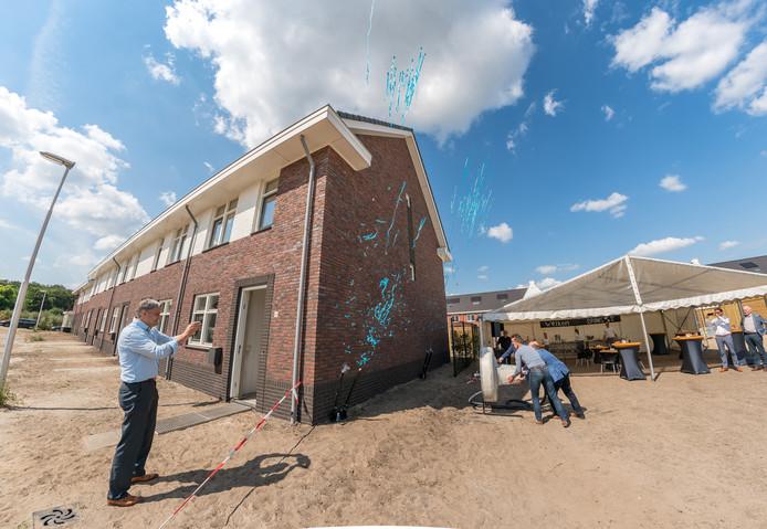 Met vereende krachten steken wethouder Roland Cornelissen, Meindert Koopman en Jan van der Spek een reuzenstekker in een 'stopcontact' bij oplevering van eerste gasloze huizen in Rijssen.