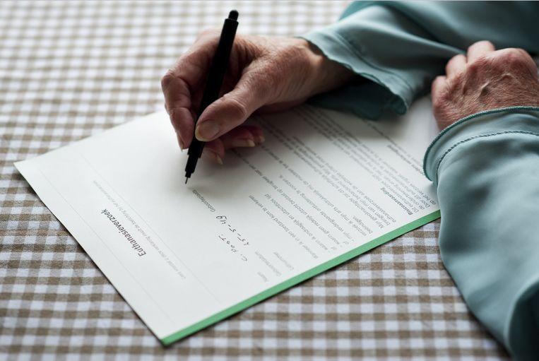Een vrouw tekent de wilsverklaring. Beeld anp xtra