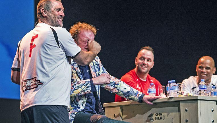 John de Wolf laat in Theater De Vest in Alkmaar zien, met spreekstalmeester Koert Westerman als slachtoffer, hoe hij ooit een tegenstander met een gebroken neus aanpakte. Ricky van den Bergh en Glenn Helder kijken toe. Beeld Guus Dubbelman / de Volkskrant