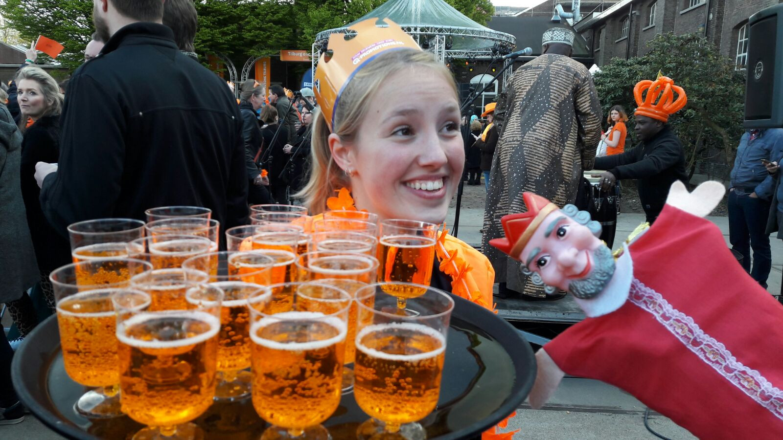 Lotte van Oudheusden (17) geeft gratis oranjebiter aan de bezoekers.