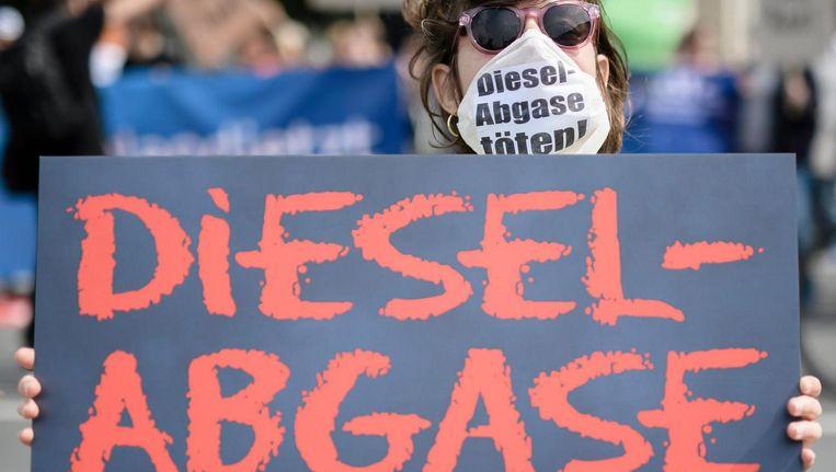 Een demonstrant voor het ministerie van Transport in Berlijn, Duitsland, draagt een masker waarop geschreven staat 'dieseluitlaatgassen doden! Beeld epa