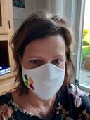 """Rina Verwijmeren uit Sprundel: """"Het mondkapje is gemaakt van een polo van onze zorginstelling DAT in Roosendaal. Heb hiervoor een polo van de zorginstelling kapot geknipt, en hun logo gebruikt. Vanwege de schaarste van mondkapjes heb ik die gemaakt."""""""