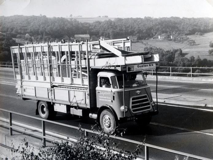 Een vrachtwagen van de firma Guelen rijdt over de Duitse snelweg met in de bak een complete PéGéwoning, karakteristiek voor de wederopbouw.