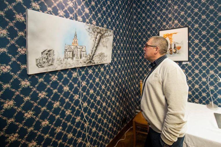 Een bezoeker bekijkt een van de werken.